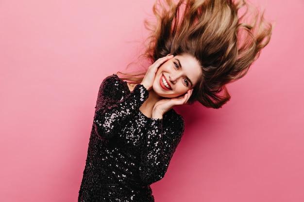Agradável garota inspirada dançando na parede rosa. linda mulher morena em traje preto, se divertindo.