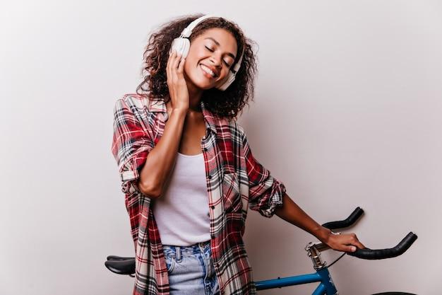 Agradável garota negra curtindo música com os olhos fechados. mulher africana atraente ouvindo música favorita durante o ensaio fotográfico com bicicleta.