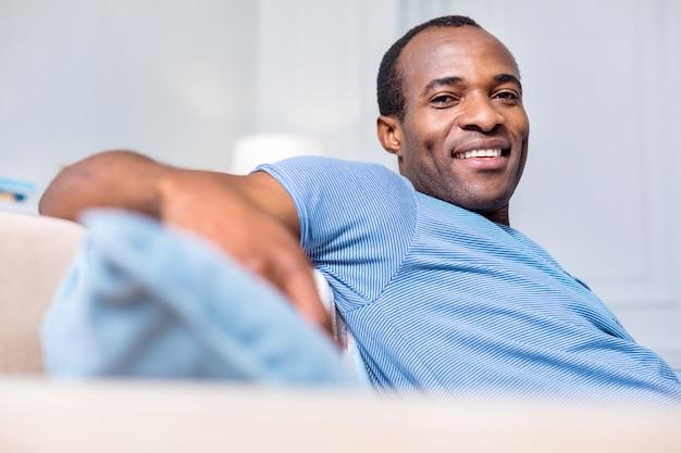 Agradável homem bonito sorrindo e olhando para você enquanto está em casa