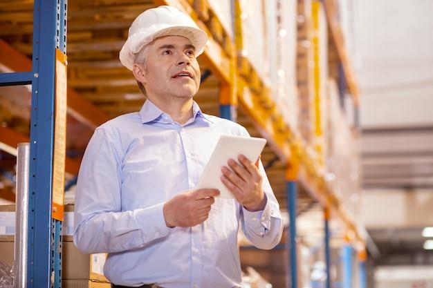 Agradável homem inteligente usando um capacete enquanto trabalhava em um depósito