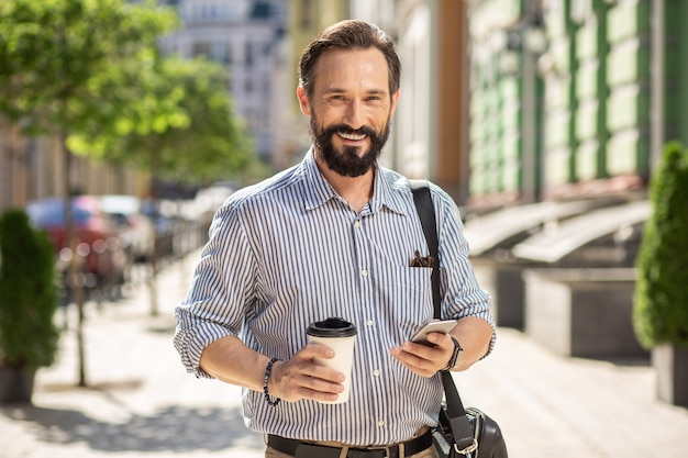Agradável hora da manhã. homem bonito alegre tomando café enquanto caminha pela rua