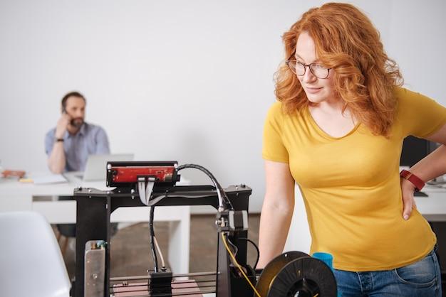 Agradável, inteligente e simpático designer olhando para a máquina de impressão 3d e observando como ela funciona enquanto está perto dela