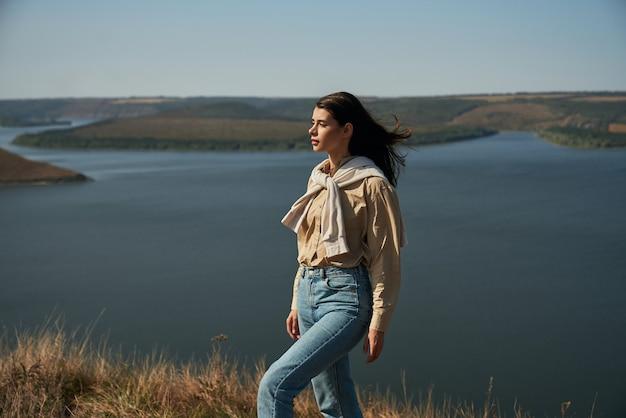 Agradável jovem com cabelo castanho, posando entre a bela paisagem do parque nacional ucraniano.