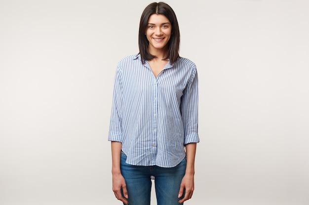 Agradável jovem morena atraente em pé, vestida de jeans e camisa listrada. menina simpática encantadora e positiva isolada