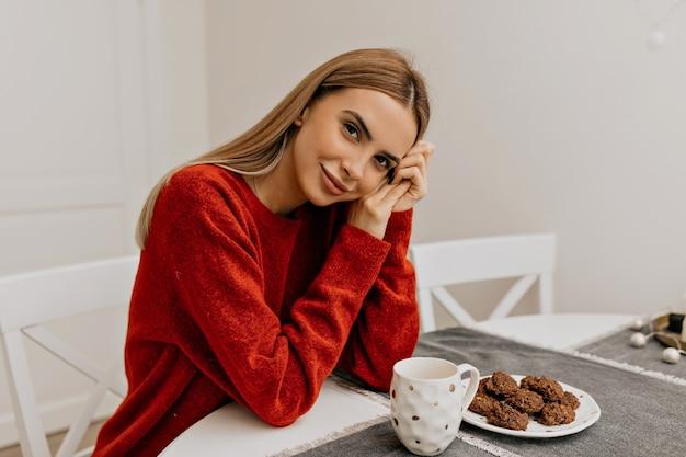 Agradável linda garota de suéter vermelho sentada de manhã na cozinha com café e biscoitos