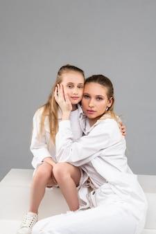 Agradável mulher adulta sentada com sua irmã mais nova, tocando suavemente sua bochecha e demonstrando amor
