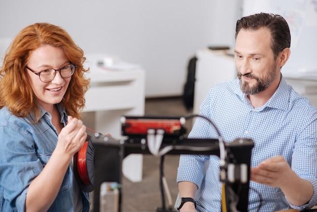 Agradável mulher bonita e inteligente segurando o filamento e assistindo com a impressora 3d trabalhar em pé com seu colega