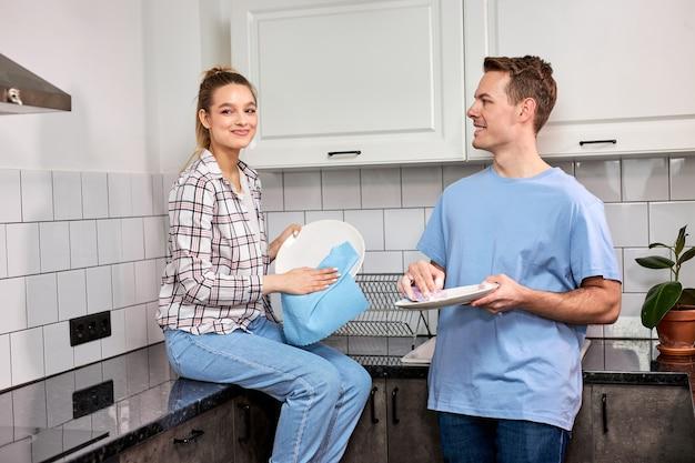 Agradável mulher caucasiana limpando pratos enquanto o marido lava na cozinha