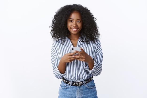 Agradável namorada afro-americana linda e amigável, vestindo uma blusa moderna e elegante segurando um smartphone, sorrindo, com uma atitude extrovertida amplamente agradável, editar selfie usando o aplicativo da internet