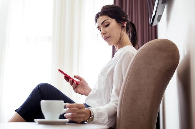 Agradável pausa para o café. mulher jovem e bonita segurando seu smartphone enquanto olha para a xícara de café