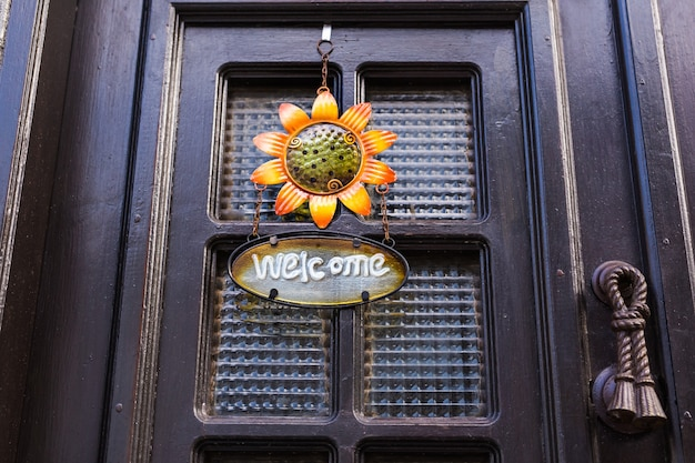 Agradável placa de boas-vindas em madeira com uma flor na porta