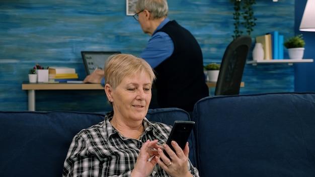Agradável senhora idosa sênior descansando no sofá usando aplicativos no smartphone, feliz velha mulher madura ...