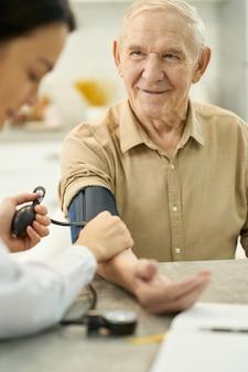 Agradecido cavalheiro idoso tendo sua pressão arterial verificada