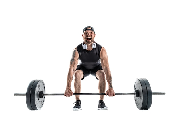 Agressivo barbudo homem forte e musculoso em roupas esportivas e fones de ouvido, fazendo um exercício de levantamento terra. comprimento total em branco.