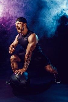 Agressivo desportista musculoso barbudo está malhando, empurre para cima com uma medicine ball isolada na parede escura com fumaça.