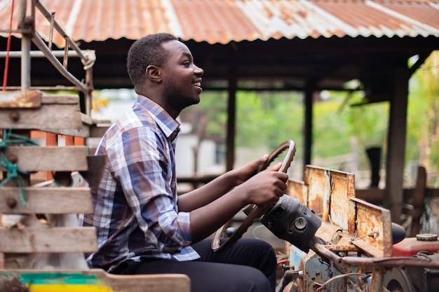 Agricultor africano dirigindo um pequeno trator no campo