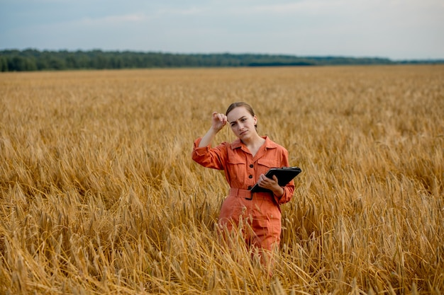 Agricultor agrônomo com computador tablet digital em campo de trigo usando aplicativos e internet smart agriculture