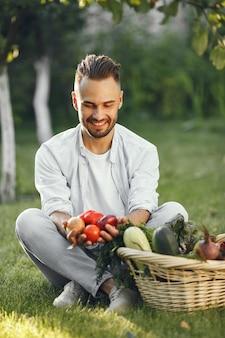 Agricultor alegre com vegetais orgânicos no jardim. vegetais orgânicos misturados em cesta de vime.