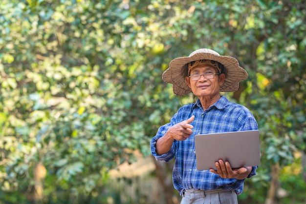 Agricultor asiático com laptop