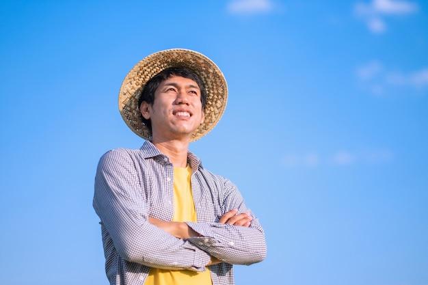 Agricultor asiático cruza os braços e sorri com o céu azul