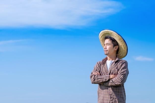 Agricultor asiático cruzando os braços sobre o céu azul com espaço de cópia