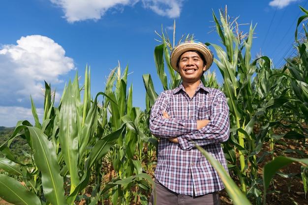 Agricultor asiático em pé de chapéu em sua fazenda no campo de milho sob o céu azul no verão