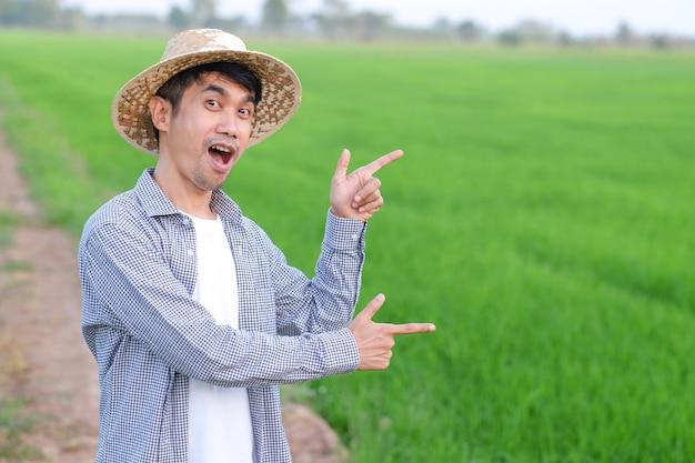 Agricultor asiático faz pose de surpresa com cara de choque em uma fazenda de arroz verde