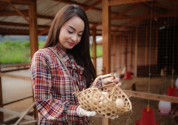 Agricultor asiático na granja segurando uma galinha ovos