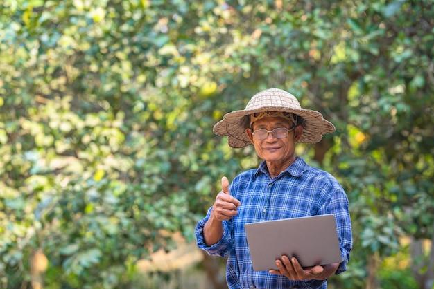 Agricultor asiático no campo com laptop
