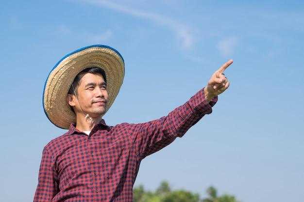 Agricultor asiático olhando e apontando o dedo para o céu azul