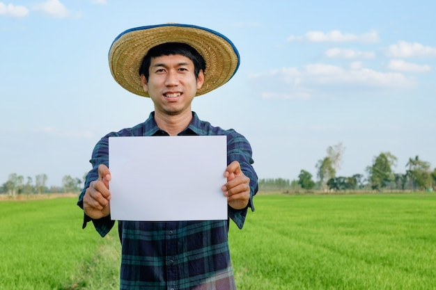 Agricultor asiático segurando papel branco em branco para apresentação na fazenda verde