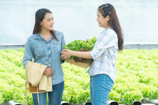 Agricultor asiático segurando uma cesta de legumes e apertar as mãos dos parceiros após o acordo ter sucesso.