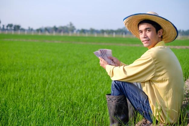 Agricultor asiático sentado e segurando o dinheiro das notas da tailândia em uma fazenda de arroz verde