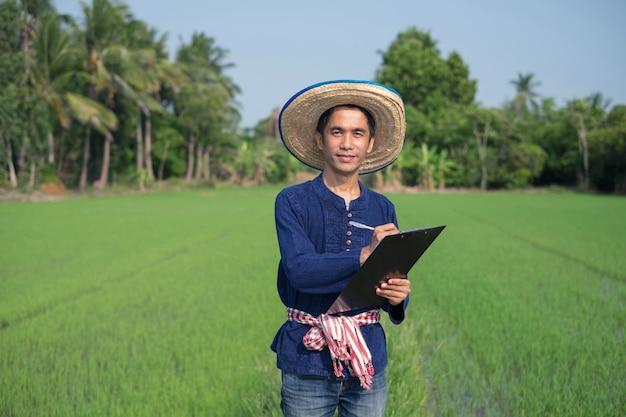 Agricultor asiático usa traje tradicional em pé e escrevendo um quadro de papel no verde