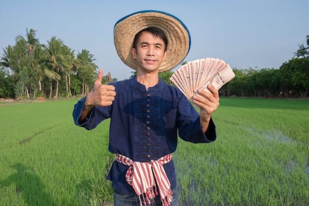 Agricultor asiático usa traje tradicional em pé e segurando dinheiro na fazenda de arroz verde