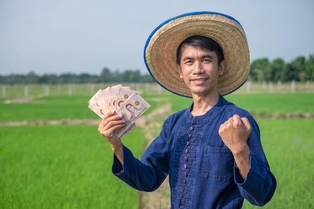 Agricultor asiático usando traje tradicional segura uma nota de dinheiro tailandês e levanta a mão para um arroz verde