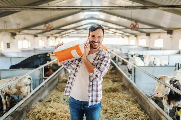 Agricultor caucasiano sorridente em pé no celeiro com um saco com comida animal por cima do ombro