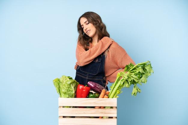 Agricultor com legumes frescos colhidos em uma caixa com dor no ombro por ter feito um esforço