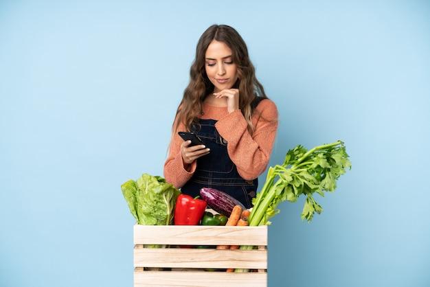Agricultor com legumes frescos colhidos em uma caixa pensando e enviando uma mensagem