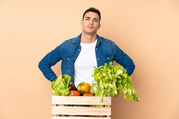 Agricultor com legumes recém colhidos em uma caixa em bege com raiva