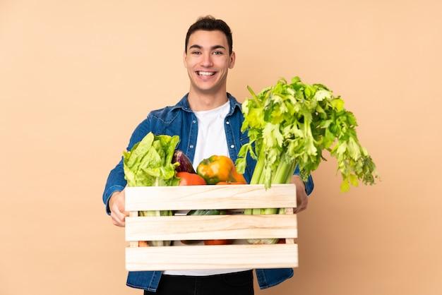 Agricultor com legumes recém colhidos em uma caixa em bege