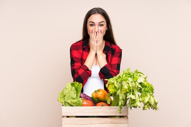 Agricultor com legumes recém colhidos em uma caixa isolada em bege com expressão facial de surpresa
