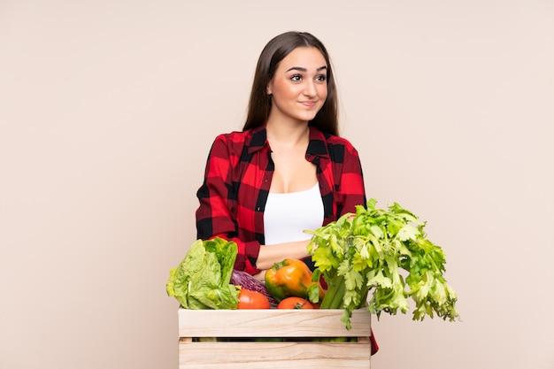 Agricultor com legumes recém colhidos em uma caixa isolada em bege, pensando uma idéia