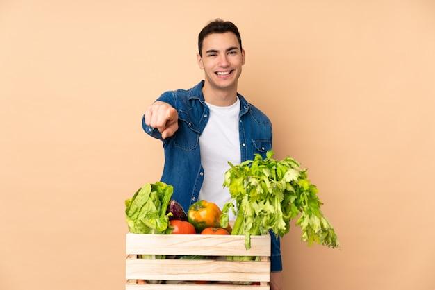 Agricultor com legumes recém colhidos em uma caixa isolada na parede bege aponta o dedo para você com uma expressão confiante