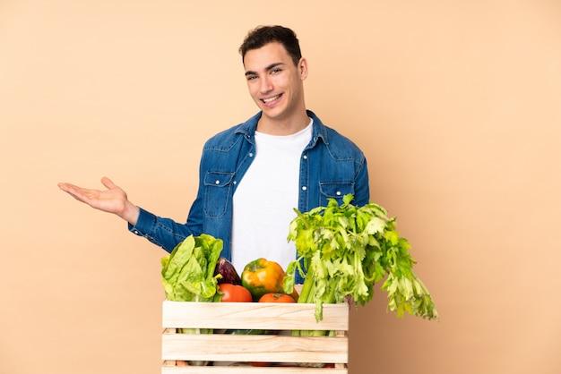 Agricultor com legumes recém colhidos em uma caixa isolada na parede bege, apresentando uma idéia enquanto olha sorrindo para