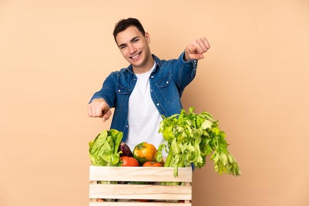 Agricultor com legumes recém colhidos em uma caixa na parede bege aponta o dedo para você enquanto sorrindo