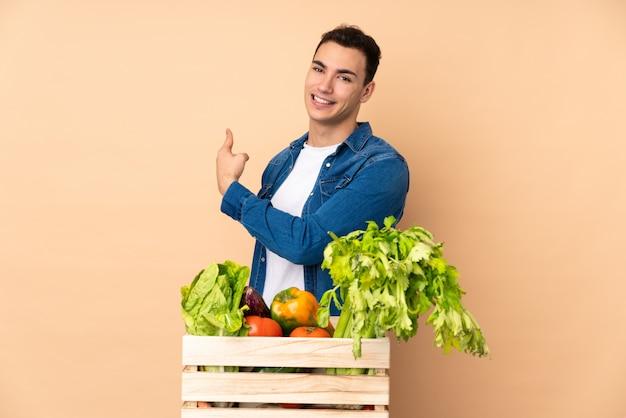 Agricultor com legumes recém colhidos em uma caixa na parede bege apontando para trás