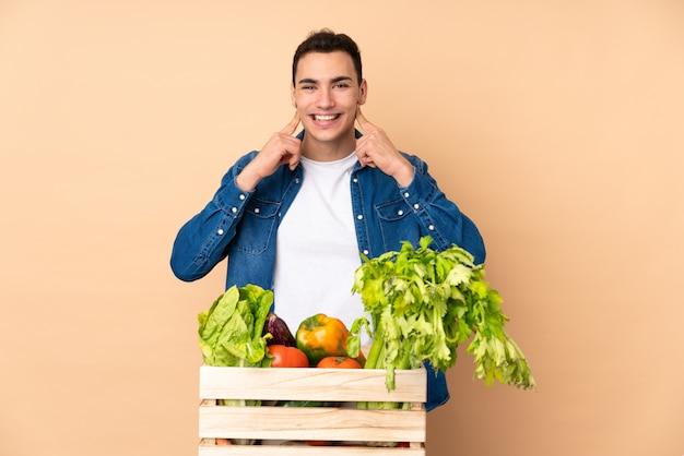 Agricultor com legumes recém colhidos em uma caixa na parede bege sorrindo com uma expressão feliz e agradável