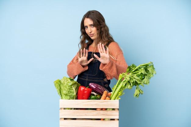 Agricultor com legumes recém colhidos em uma caixa nervosa, esticando as mãos para a frente