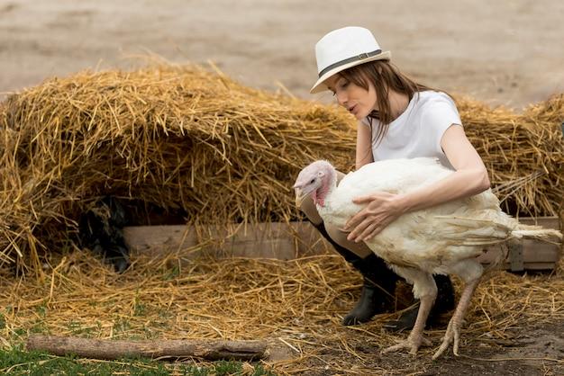 Agricultor com um peru em uma fazenda